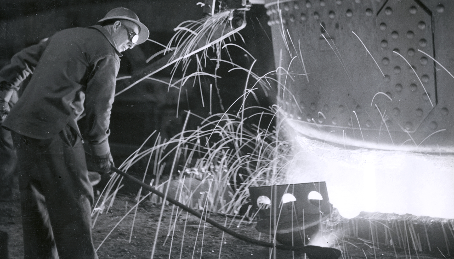 Steelworker near large machinery with sparks